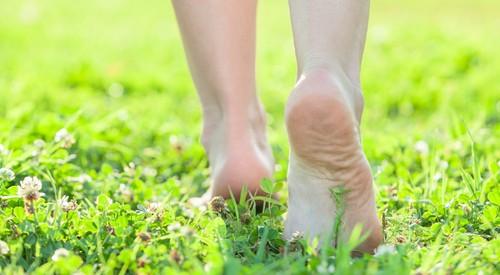 женщина идёт без обуви по траве